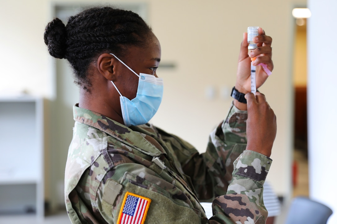 A soldier wearing a mask holds a syringe with the needle inserted into a small bottle.