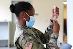 Army Pfc. Shaniah Edwards, assigned to the Virgin Islands Army National Guard's medical detachment, prepares to administer the Moderna COVID-19 vaccine to soldiers and airmen at the Joint Force Headquarters in Kingshill, Virgin Islands, Feb. 12, 2021.