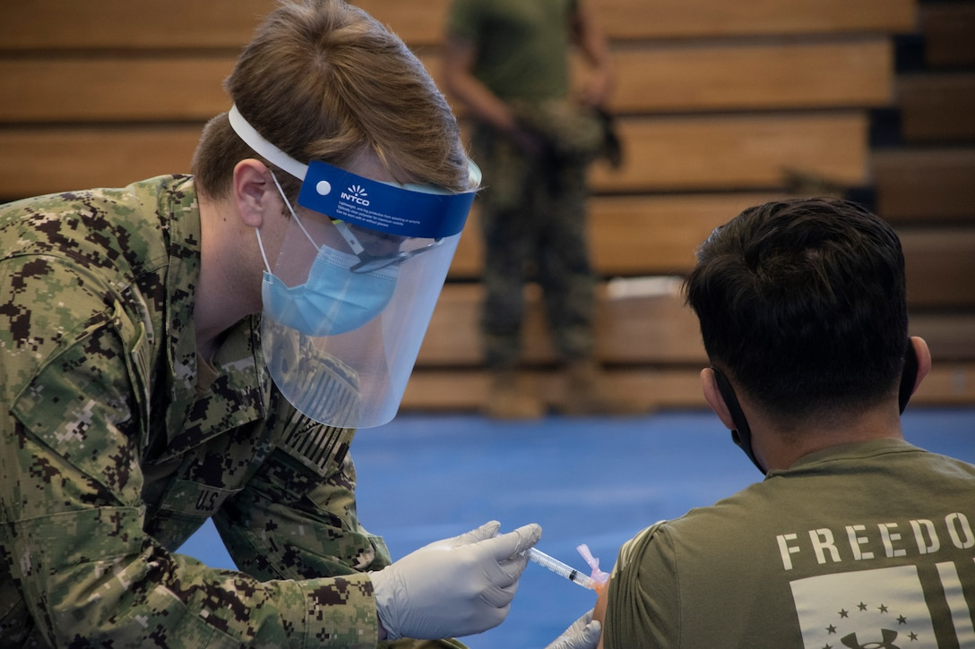 U.S. Navy sailor prepares a Marine for their first dose of the Moderna COVID-19 vaccine, Gotemba, Japan, Feb. 18.