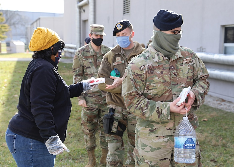 Karen Hunt, Wright-Patterson United Service Organizations (USO) volunteer, passes out chicken sandwiches to members of the 445th Airlift Wing Jan 9., 2021.
