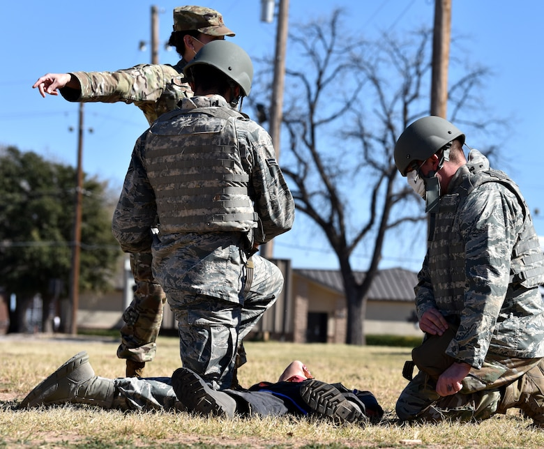 U.S. Air Force Maj. Iveth Galvez Guzman, 17th Medical Group flight commander of military medicine, shouts out simulated injuries located on a mannequin to Tactical Combat Casualty Care course participants behind the Airman and Family Readiness Center on Goodfellow Air Force Base, Texas, Feb. 7, 2021. During the course, participants had to react quickly to simulated injuries explained by instructors or play the role of victim.  (U.S. Air Force photo by Staff Sgt. Seraiah Wolf)