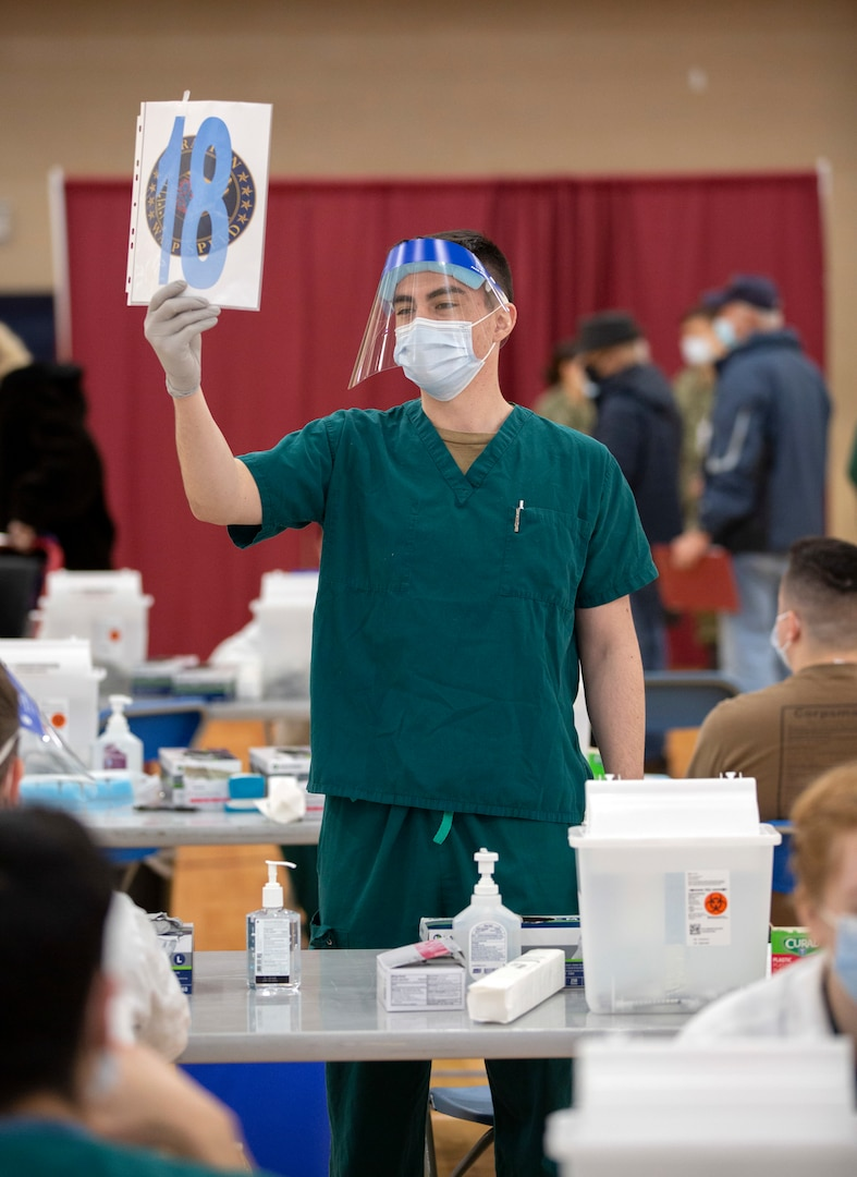 Petty Officer 3rd Class Charles Cambern holds up a numbered sign as patients circle through to receive the COVID-19 vaccine as part of Operation Warp Speed at Walter Reed National Military Medical Center Jan. 14.
