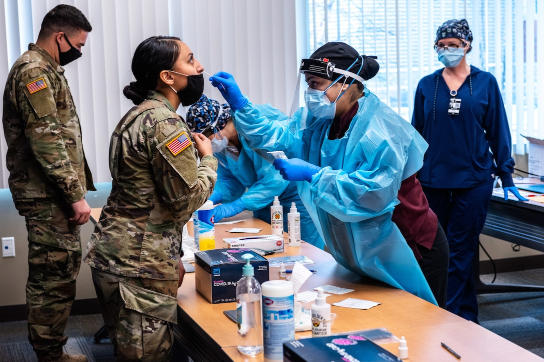 A woman wearing personal protective equipment swabs the nose of a service member, as another service member stands at a table in front of another person wearing personal protective equipment.