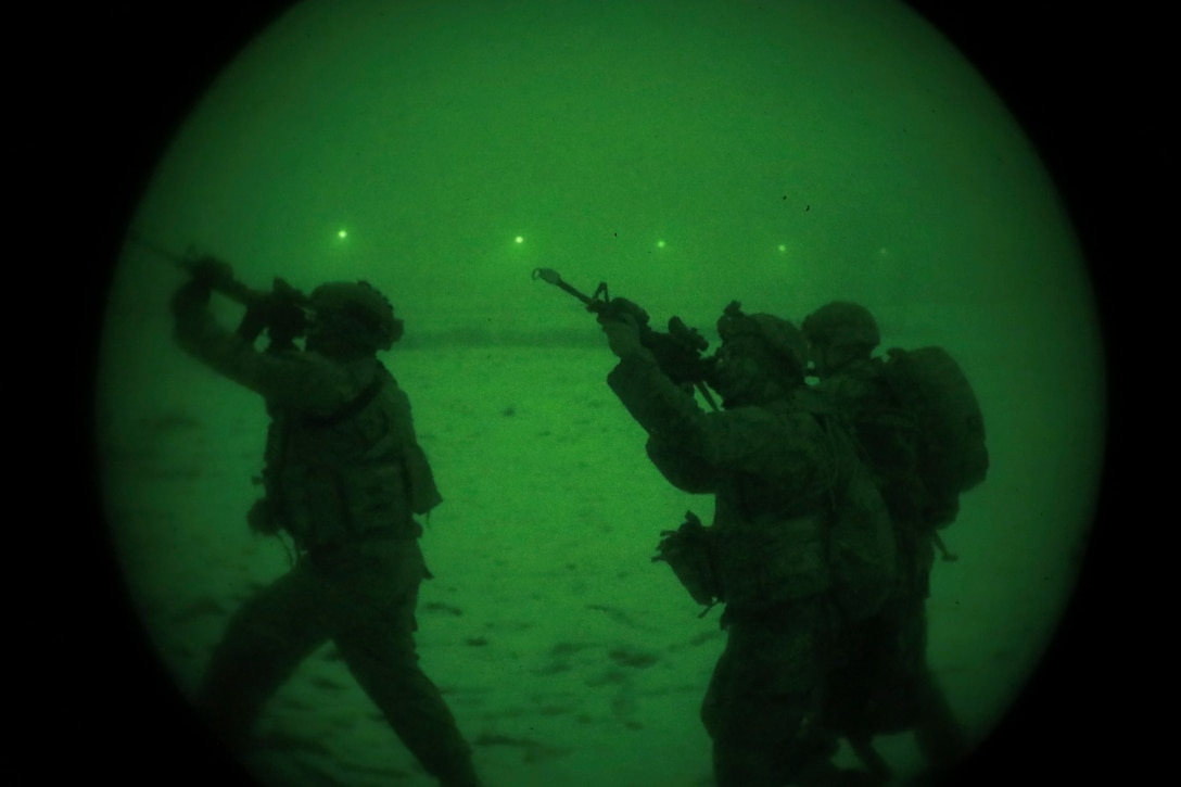 Soldiers aim weapons as seen through night vision lens.