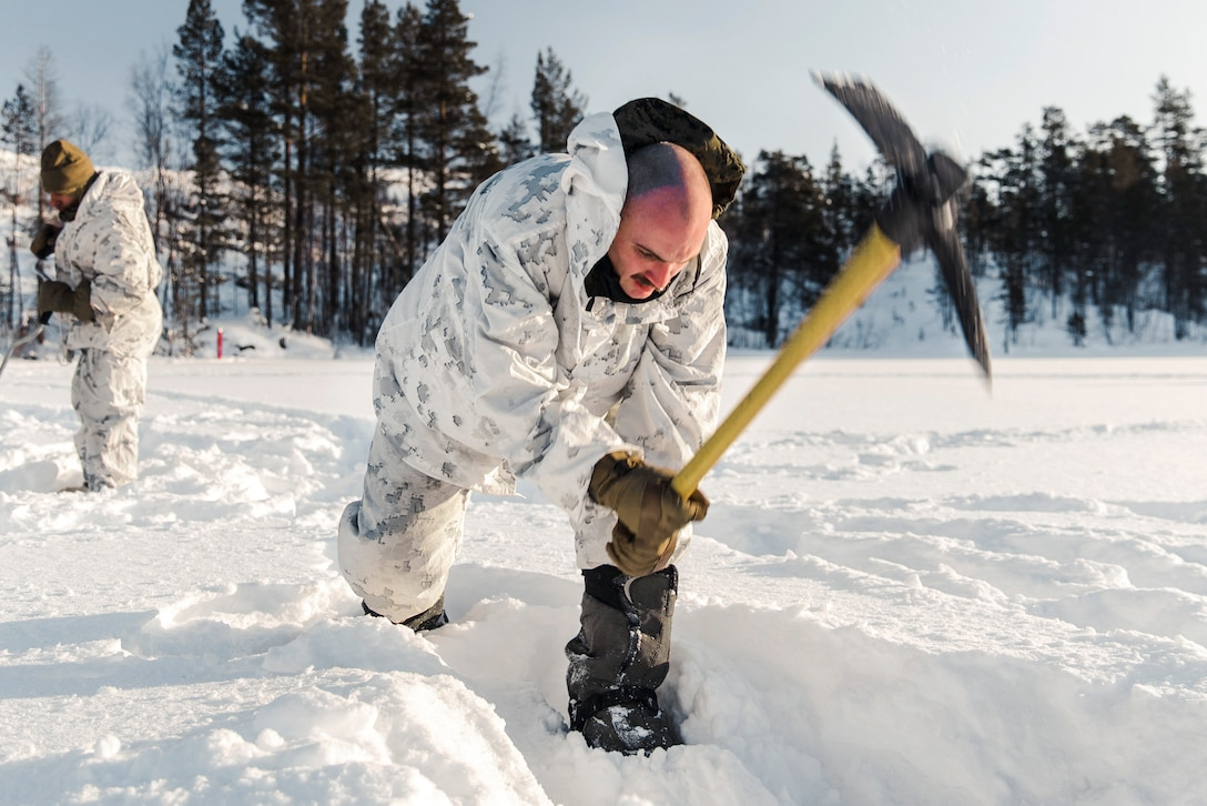A Marine uses a tool to break ice.