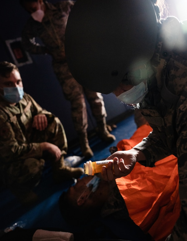 U.S. Air Force Capt. Amber Gibbons, 17th Operational Medical Readiness Squadron officer in charge of the student clinic, examines a prop prescription bottle while assessing a patient during the final exercise of the Tactical Combat Casualty Care course at the Mathis Fitness Center on Goodfellow Air Force Base, Texas, Feb. 7, 2021. During the exercise, candy was used to imitate the combat pill pack, which allowed the medics to administer the needed 'medication' based on simulated injuries. (U.S. Air Force photo by Senior Airman Deven Schultz)