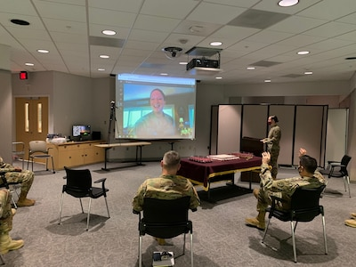 Soldiers sitting in chairs in a classroom while a soldier is talking virtually and shown on a movie screen.