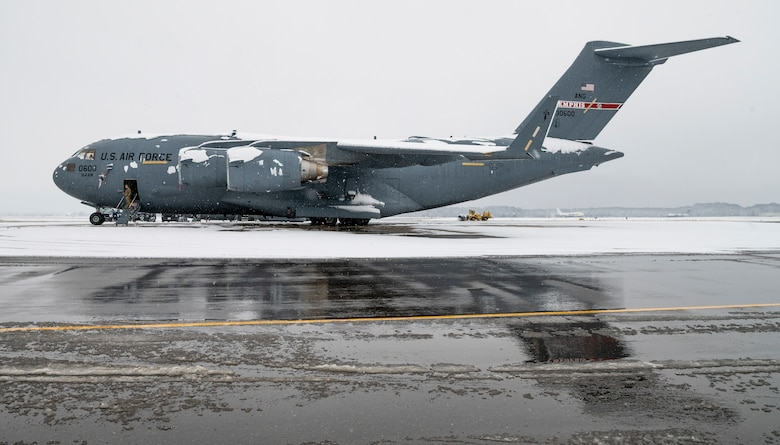 A snow-covered Tennessee Air National Guard C-17 Globemaster III sits on the flight line at Dover Air Force Base, Delaware, Feb. 11, 2021. As snow fell, the base continued normal operations and prepared for additional winter weather. (U.S. Air Force photo by Senior Airman Christopher Quail)