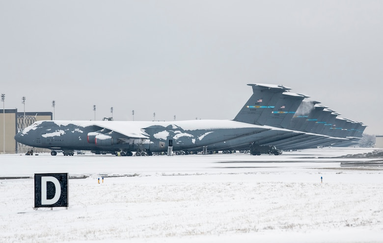 Snow-covered C-5M Super Galaxy aircraft sit on the flight line at Dover Air Force Base, Delaware, Feb. 11, 2021. As snow fell, the base continued normal operations and prepared for additional snowfall. (U.S. Air Force photo by Senior Airman Christopher Quail)