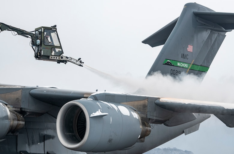 A de-icing vehicle removes snow from the left wing of a transient C-17 Globemaster III, assigned to the 62nd Airlift Wing Joint Base Lewis-McChord, Washington, prior to departing Dover Air Force Base, Delaware, Feb. 11, 2021. Because snow and ice can change the shape of an aircraft's wings and tail, the de-icing process is very important in ensuring a smooth and safe flight. (U.S. Air Force photo by Senior Airman Christopher Quail)