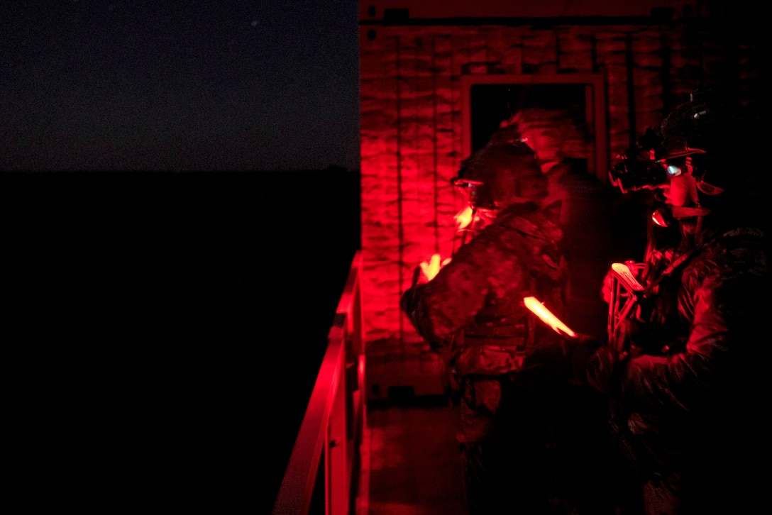 Airmen are seen in red light while holding lights during a night exercise.