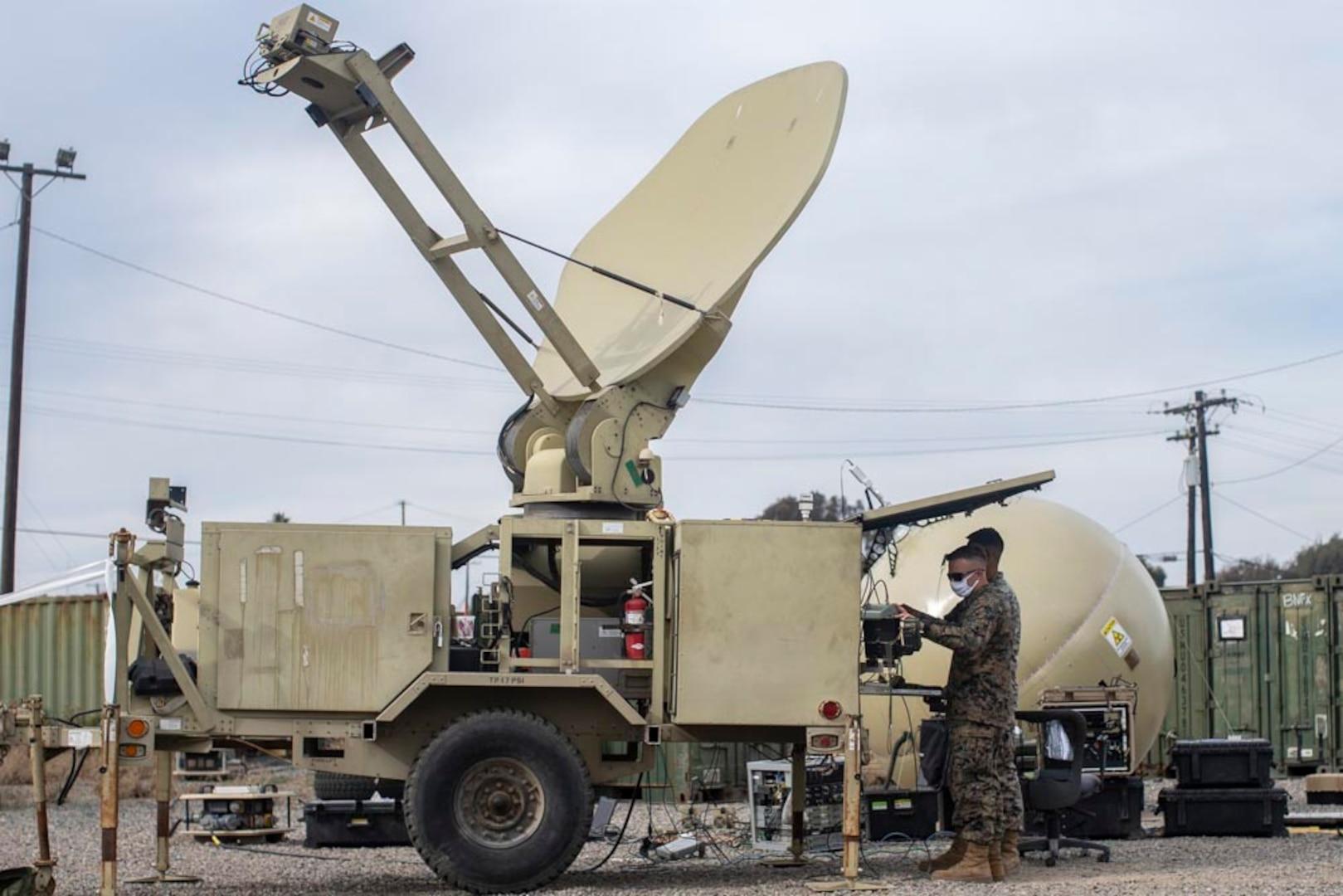 Marines work on satellite gear.