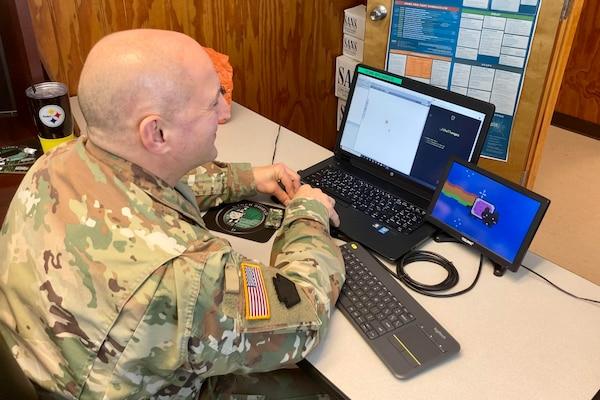 A man in a uniform types on a laptop.
