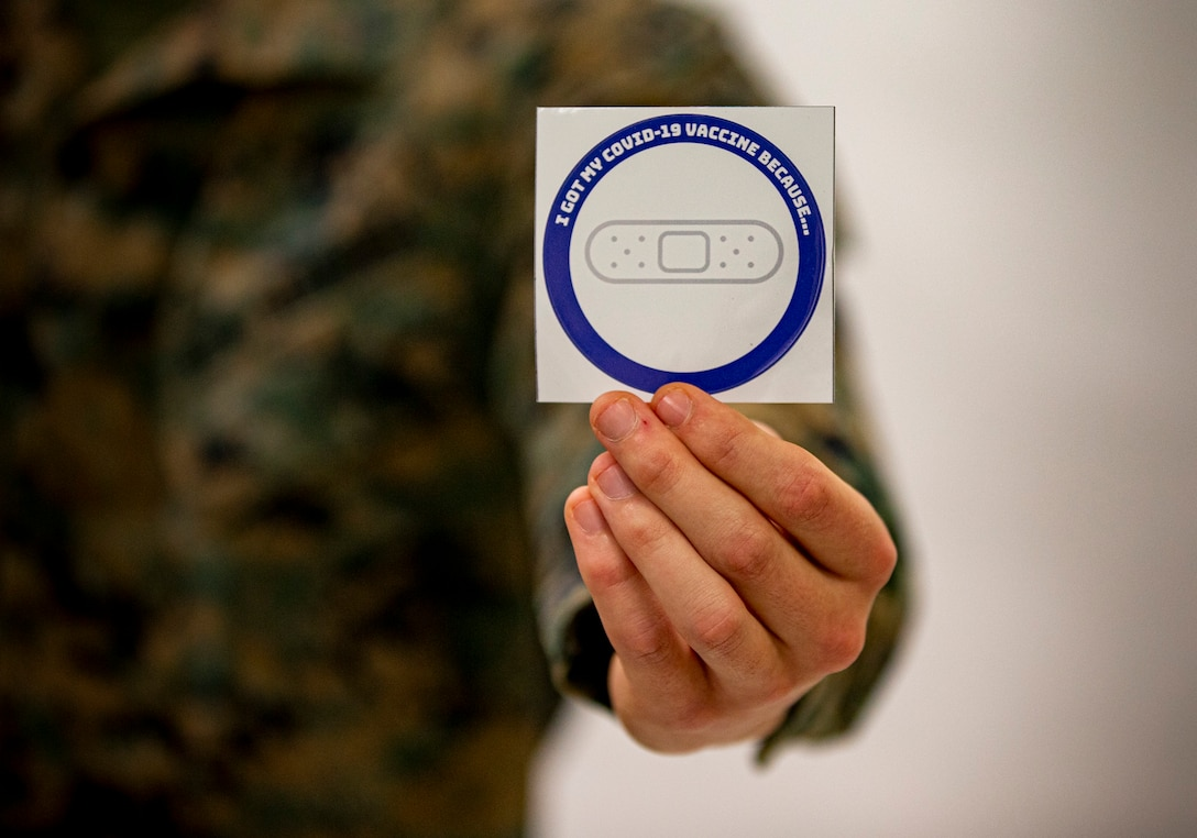 CAMP FOSTER, Okinawa (Feb. 19, 2021) A U.S. Marine holds out a sticker given to Marines after receiving the COVID-19 vaccination at the U.S. Naval Hospital Okinawa, on Camp Foster, Feb. 18, 2020. As thousands of service members are receiving the COVID-19 vaccination, they are given a sticker stating �I got my COVID-19 vaccine because�� This personal memento signifies their own unique reason to receive the vaccine. (U.S. Marine Corps  photo by Staff Sgt. Lucas Vega)