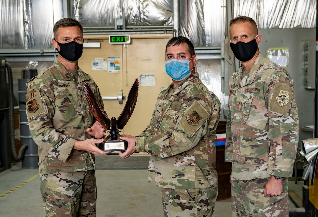 U.S. Air Force Maj. Christopher Smith, 380th Expeditionary Maintenance Squadron commander (center), accepts the 2020 Air Combat Command Maintenance Effectiveness Award for small aircraft maintenance at Al Dhafra Air Base, United Arab Emirates, Feb. 22, 2020.