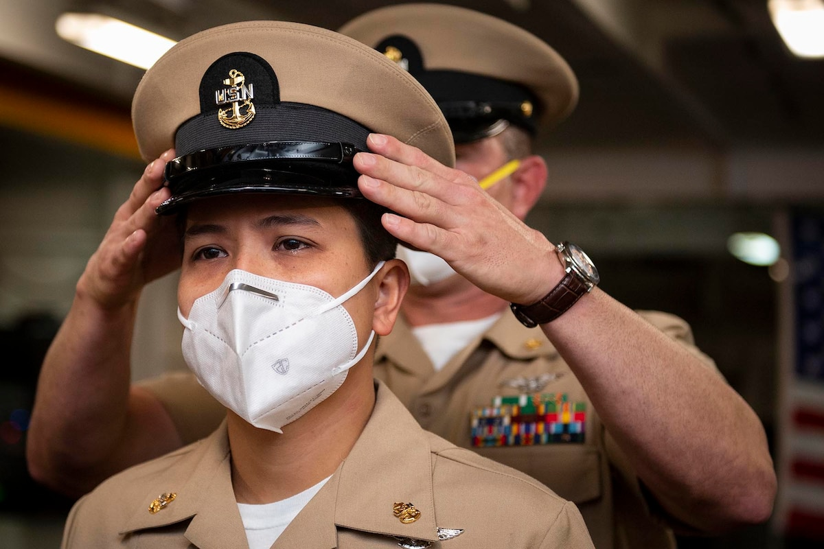A Navy cover is placed on the head of a sailor by another sailor standing behind her.