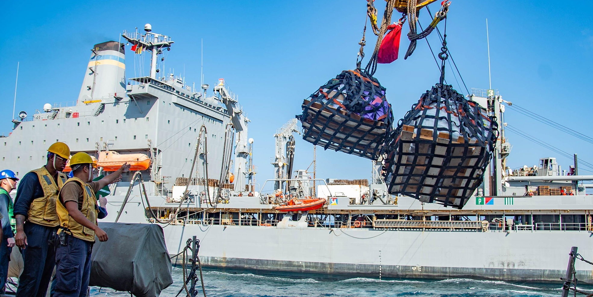 Sailors aboard the guided-missile destroyer USS Winston S. Churchill (DDG 81) send pallets to the fleet replenishment oiler USNS Leroy Grumman (T-AO 195) during a replenishment-at-sea in the Arabian Sea, Jan. 19, 2021.