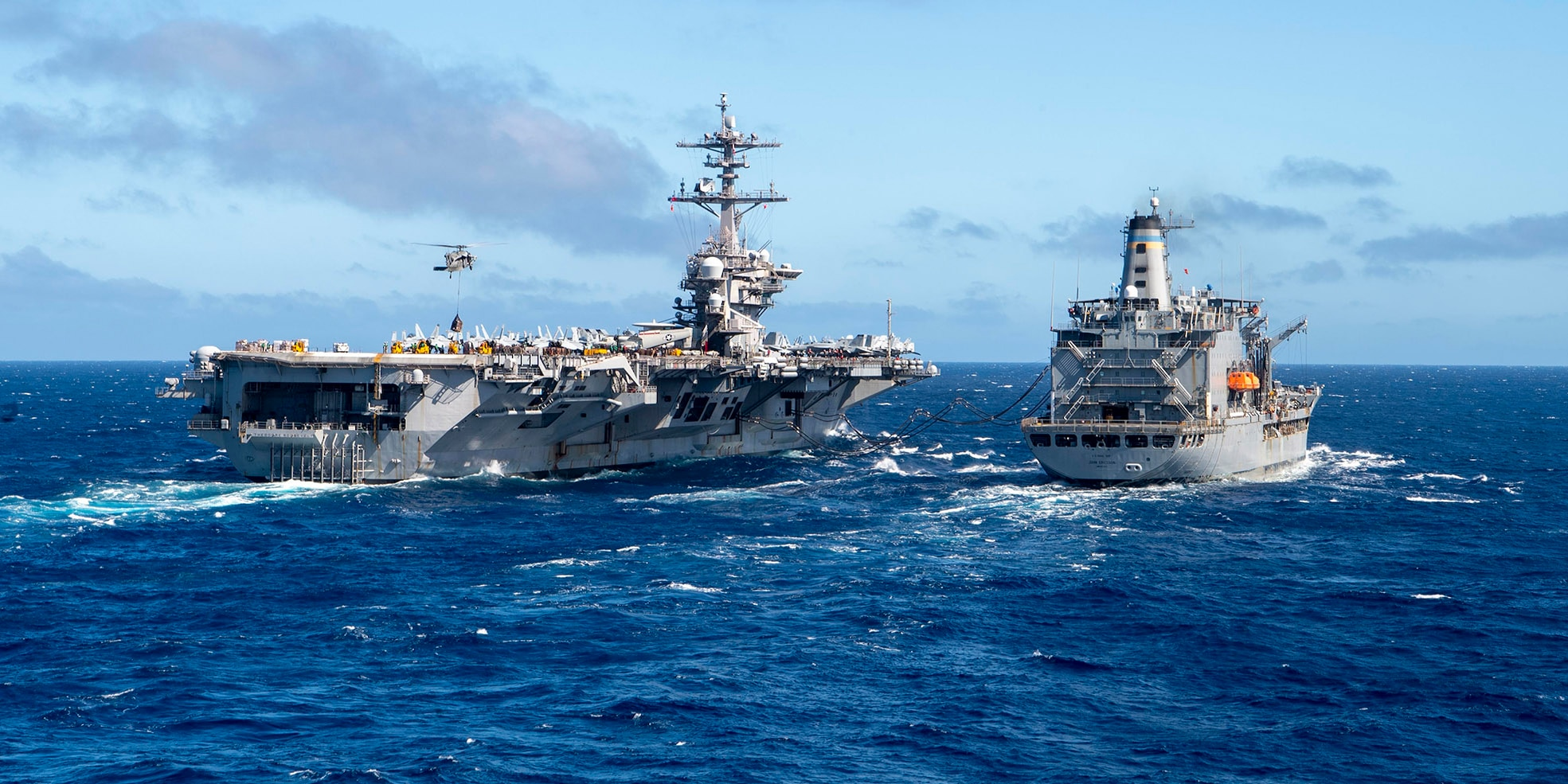 The aircraft carrier USS Theodore Roosevelt (CVN 71), left, receives fuel and supplies from the Military Sealift Command fleet replenishment oiler USNS John Ericsson (T-AO 194), Jan. 16, 2021.
