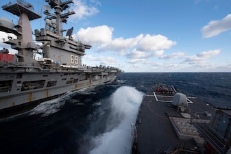 USS Mitscher (DDG 57) is underway with USS Dwight D. Eisenhower (CVN 69).