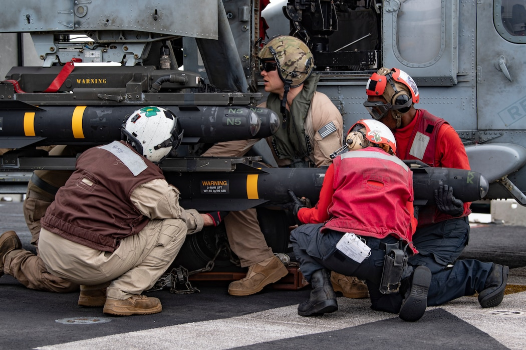 Sailors  and Marines load an AGM-114 Hellfire missile onto an MH-60S Sea Hawk helicopter