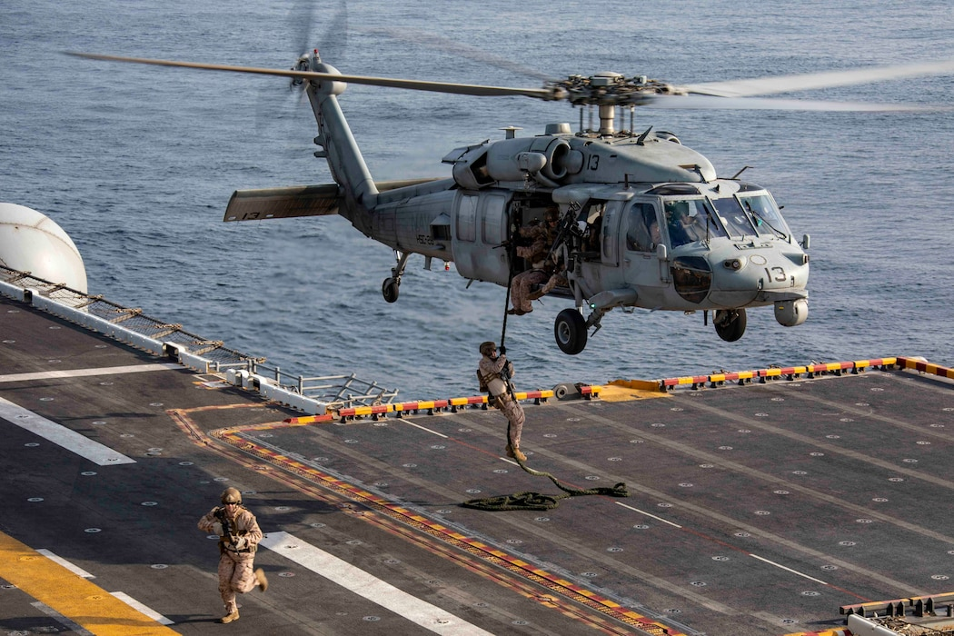 Reconnaissance and infantry Marines of the 22nd Marine Expeditionary Unit Maritime Raid Force fast-rope from an MH-60S Sea Hawk onto the flight deck of the Wasp-class amphibious assault ship USS Kearsarge (LHD 3)