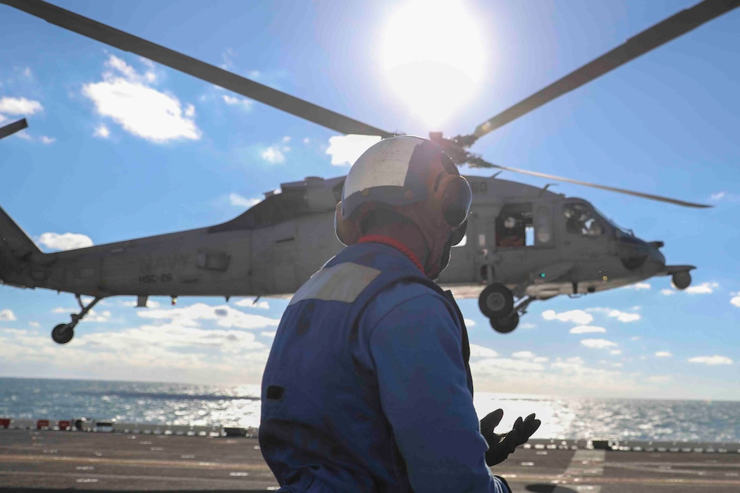 Sailor in front of helicopter