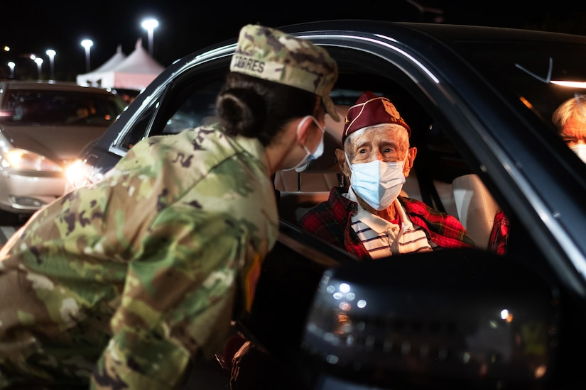 A soldier wearing a face mask leans over to a car window to talk to an elderly man wearing a face mask.
