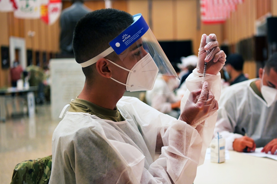 An airman wearing personal protective equipment holds a syringe while inserting the needle into a small bottle.