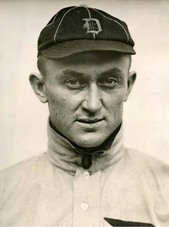 A man in a baseball uniform poses for a photo.