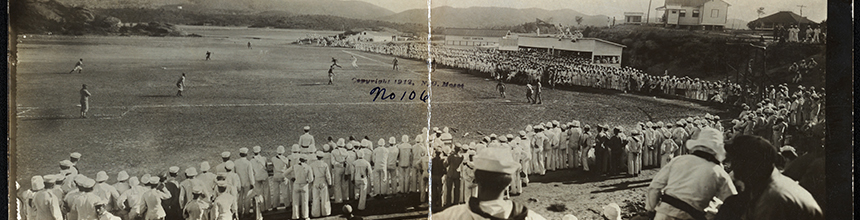 Black and white photo of baseball field with players lined along the sidelines