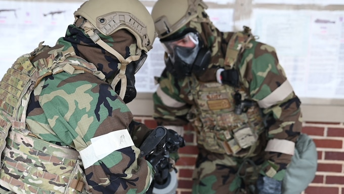 188th Security fForces squadron members inspect an M4 weapon while wearing gas masks.