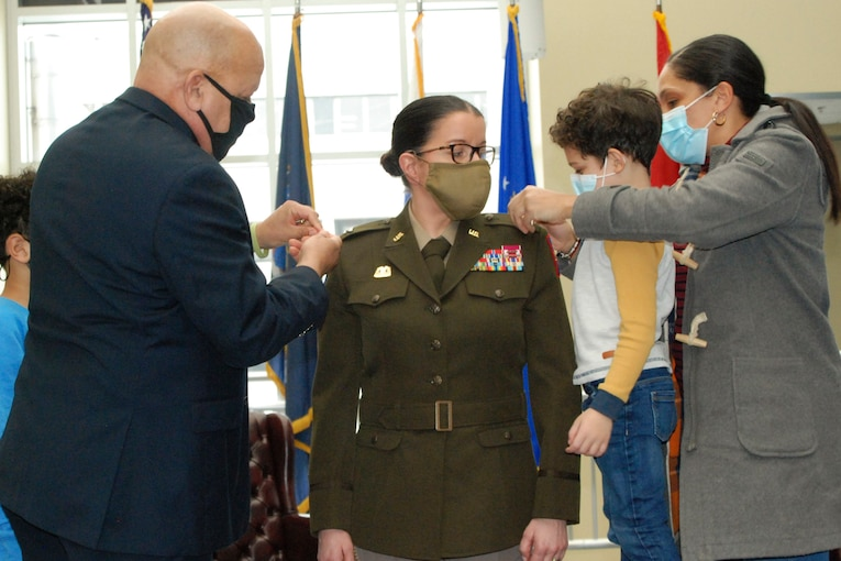 Family members pin a soldier during a ceremony.