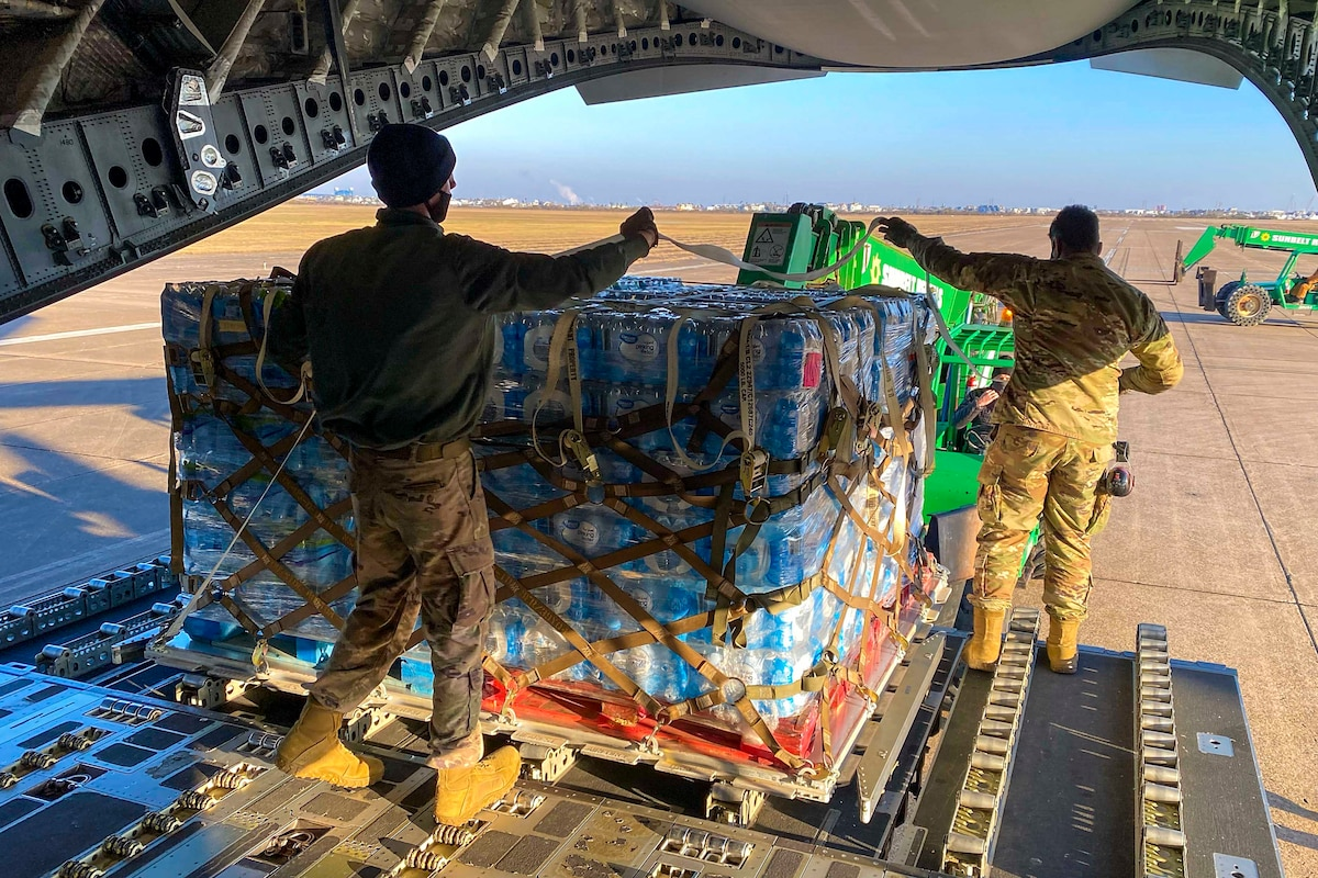 Two airmen move a pallet of bottled water at the back of an aircraft.