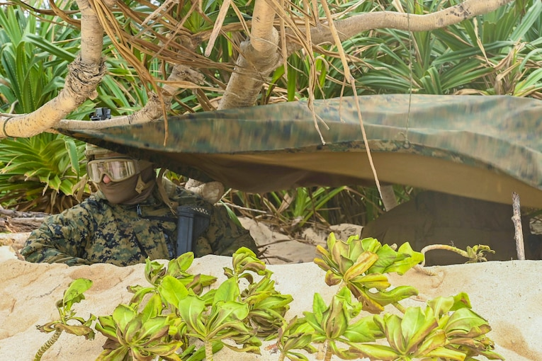 A Marine stands in a sandy hole underneath a tarp.