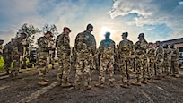 A group of soldiers stand in a group and await orders as the sun rises overhead.
