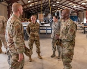 Five soldiers and Airmen wearing fatigues stand in a circle in a staging facility and talk.