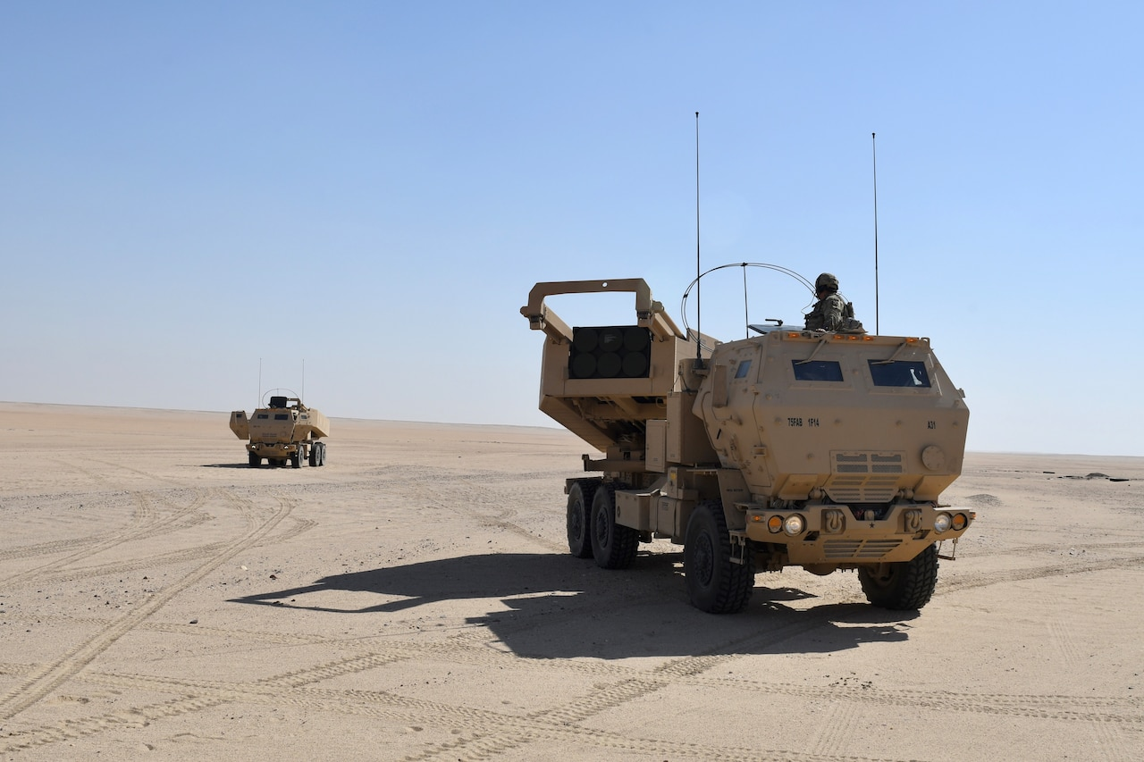 Tactical vehicles advance through desert.