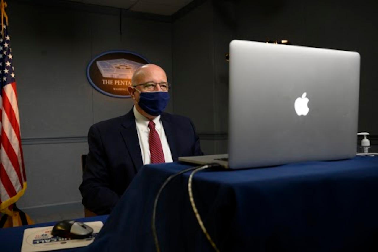 A man speaks virtually at a symposium.