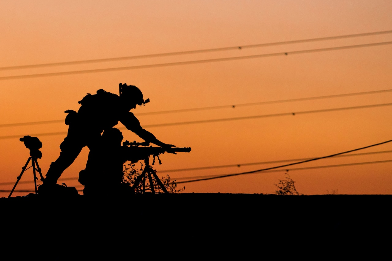 A soldier adjusts a weapon in silhouette.