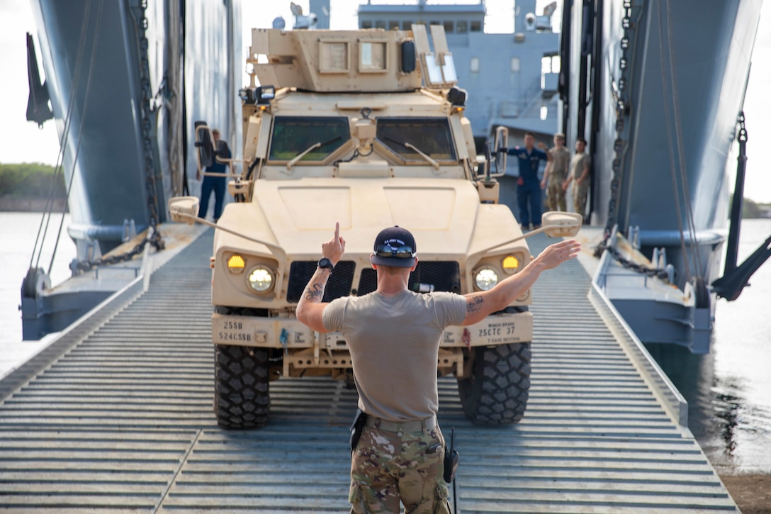 A soldier gives signals to the driver of a military vehicle aboard a water vessel.