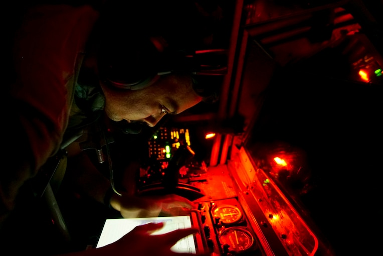 An airman in orange light handles controls inside an aircraft.
