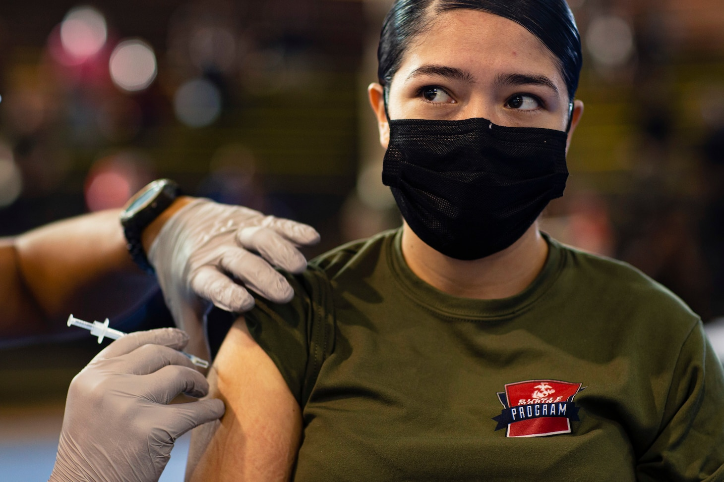 A Marine wearing a face mask receives a COVID-19 vaccine
