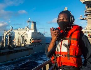 A Sailor communicates with USNS John Ericsson (T-AO 194) during a replenishment-at-sea aboard USS Theodore Roosevelt (CVN 71).