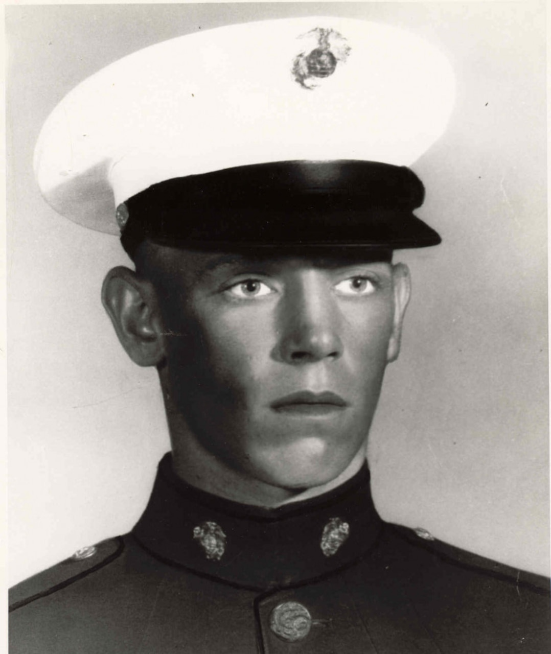 A young man in uniform and cap poses for a photograph.