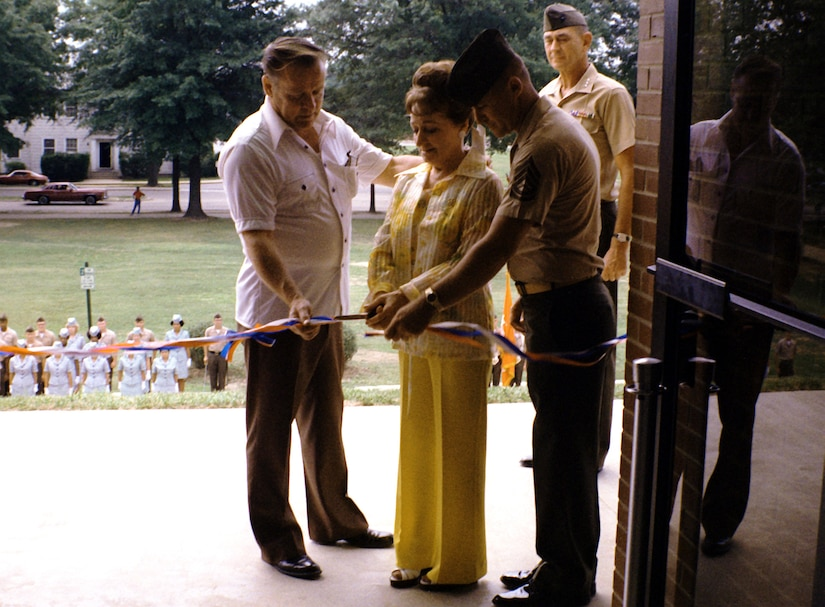 Three people stand together to cut a ribbon at the door of a building. Several people watch at the bottom of several steps.