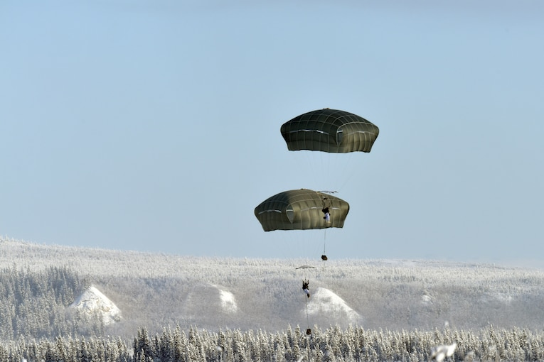 Two paratroopers descend over wintry terrain.