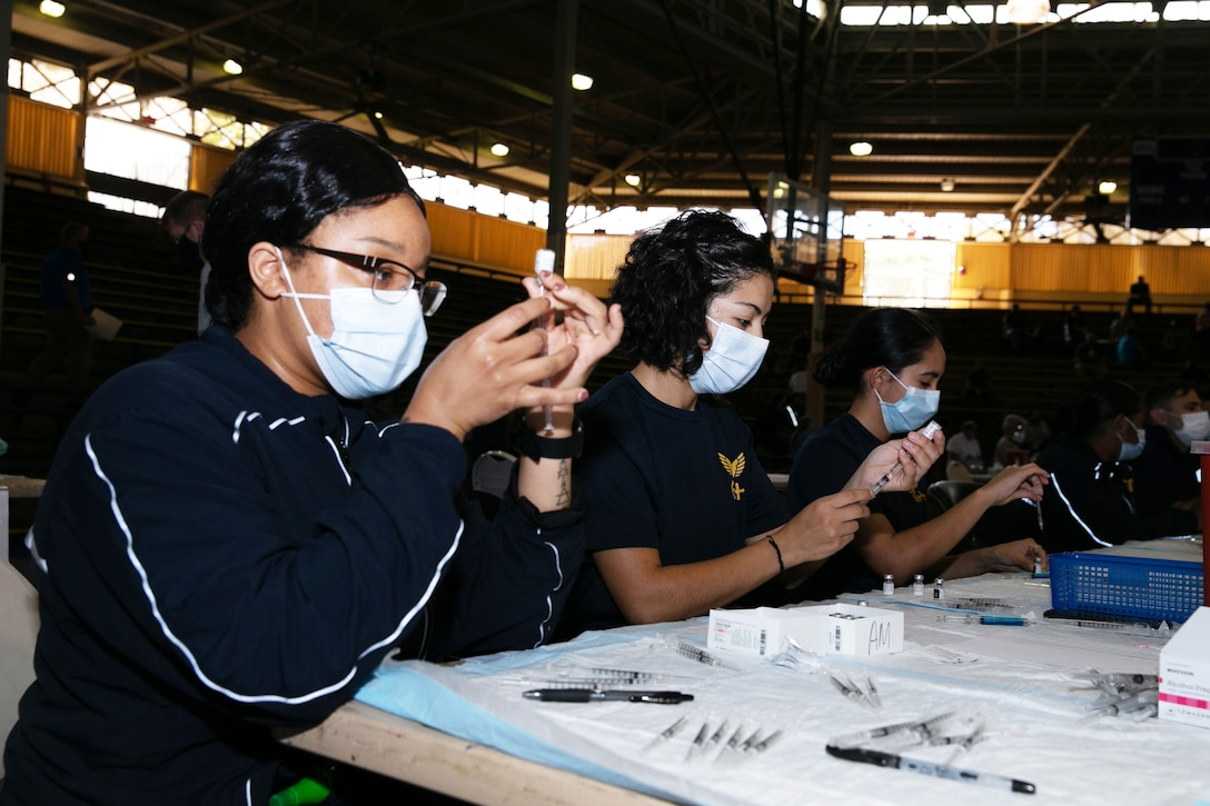 Three women wearing face masks sit at a table using syringes to draw fluid from small bottles.