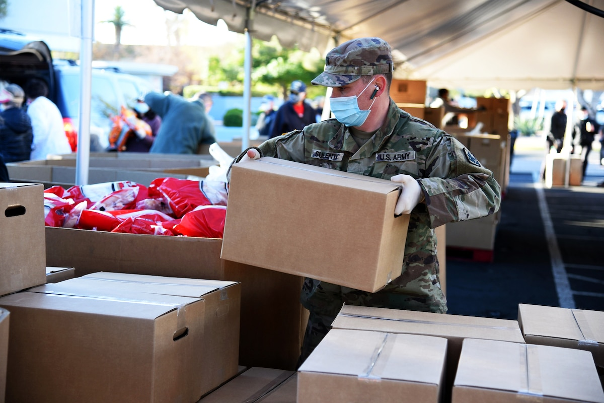 Outside under a tent, a soldier wearing a face mask and gloves picks up a box; other boxes are stacked up in front of him.