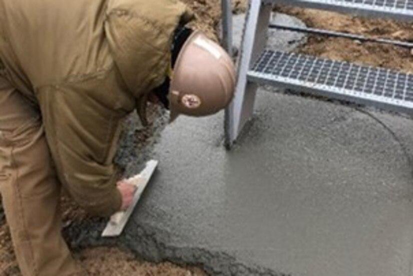 A person lays concrete.