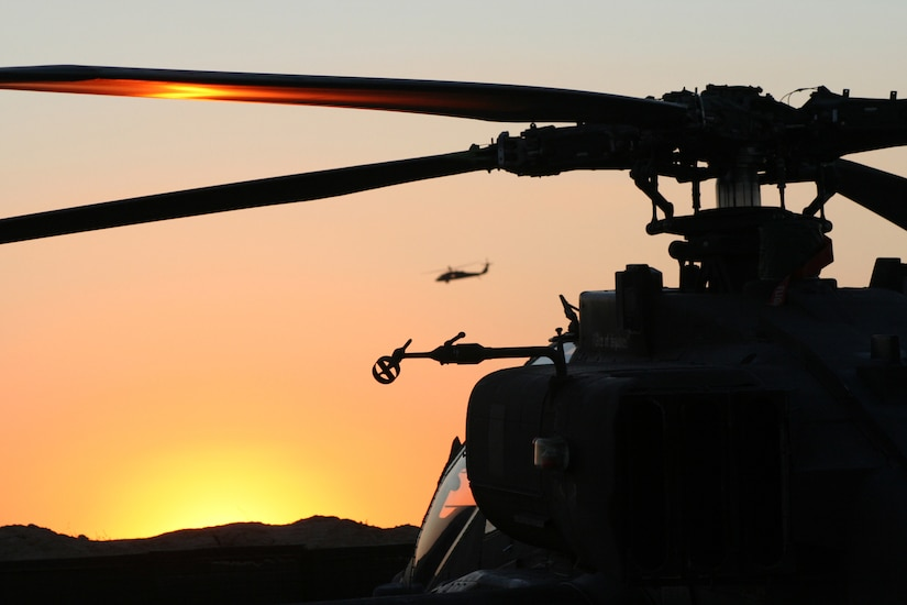 A helicopter sits in silhouette at dusk.
